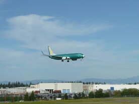 Noch unlackierte B737 im Landeanflug auf das von Boeing als Werksflugplatz benutzte Paine Field, im Hintergrund das Boeing-Flugzeugwerk in Everett.